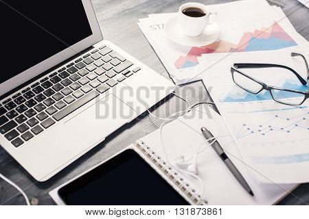 Closeup of wooden office table with blank white laptop screen tablet coffee business report and other objects