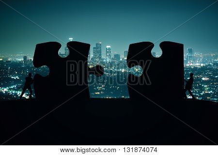 Partnership concept with businesspeople silhouettes putting puzzle pieces together on night city background