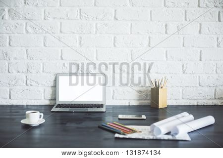 Blank laptop with white screen on wooden desktop with coffee cup pencils paperwork and other items on white brick background. Mock up