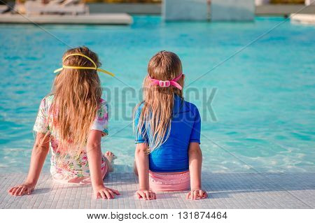 Cute toddler girls standing in shallow water at exotic beach