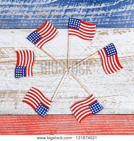 Small USA flags forming pinwheel formation on red white and blue rustic boards. Fourth of July holiday concept for United States of America.