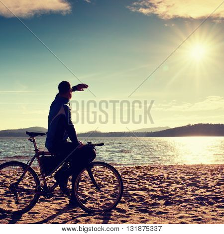 Young Man Cyclist Sit On Bike,  Blue Sky And Sunset Background On Beach. End Of Season At Lake And P