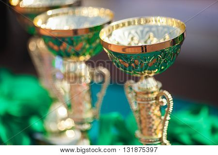 Victorious cups in sports meets. Cups of winners. Trophy cups.