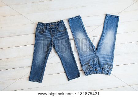 Pair of jeans on a white wooden background. Blue jeans. Clothes on a white background.