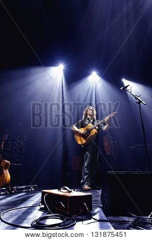 Guitarist performing music under lights on a stage.