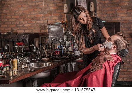 Female barber shaving a client's beard while sitting in a chair in a barber shop