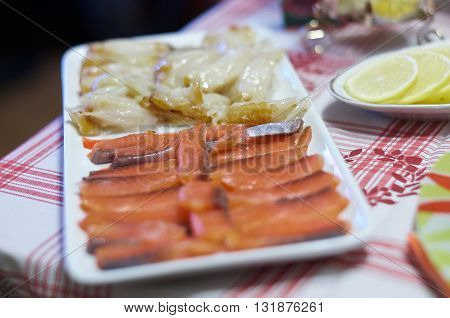 Sliced fillet of salmon and halibut on a platter. Whitefish red fish lemon slices. Gravadlax fish cuts