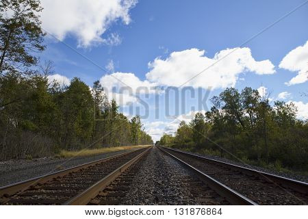 Railroad lines fade into the distant horizon under the cloudy blue skies of Western New York State. The image shows the steel rails wooden railroad ties and the gravel track bed along with various equipment necessary to move millions of tons of freight