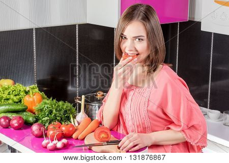 Beautiful young woman standing in the kitchen at the table full of vegetables and eating a slice of tomato