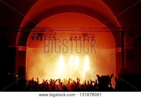 Silhouettes of huge concert crowd in front of bright stage lights with the whole stage view