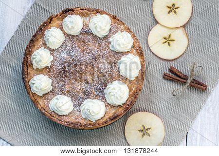 Top View on Apple Pie with Whipped Cream with Cinnamon and Apple Slices on White Table