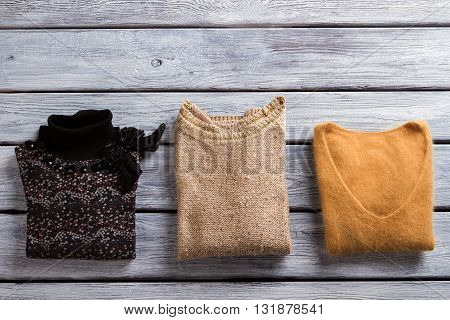 Sweaters of different color. Folded pullovers on wooden background.