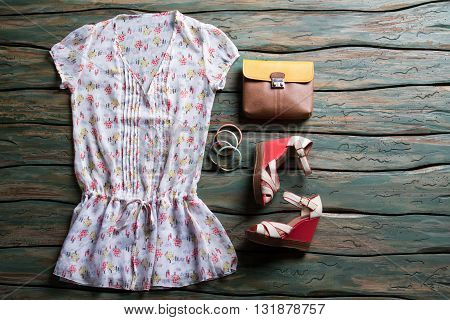 White blouse and wedge sandals. Bicolor brown purse and bracelets. Clothing on green wooden. Lady's outfit with stylish footwear.