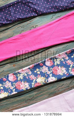 Pieces of fabric with print. Colorful cloth on wooden background. Custom clothing at fair price. Quality materials in stock.
