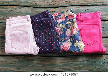 Bright pink casual pants. Folded trousers of dark color. New garments in showroom. Spring clothes collection on display.