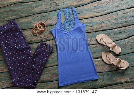Dotted trousers and blue top. Beige sandals with navy pants. Fashionable clothes in brand store. All prices have dropped.