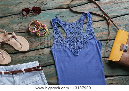 Blue top and sunglasses. Brown and orange purse. Stylish accessories in brand store. Lady's bracelets on wooden table.