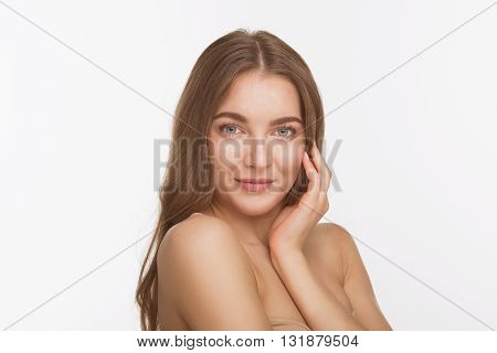 Studio shot. Beauty concept. Closeup portrait of shirtless or topless lady looking at camera and touching her face over white background.