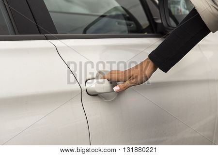 a girl holds the handle of the door white passenger car