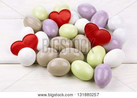 Sugared almonds with red heart shaped confetti on white wooden background
