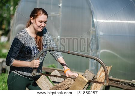 Happy girl is sawing a wooden beam the hand saw in the garden.