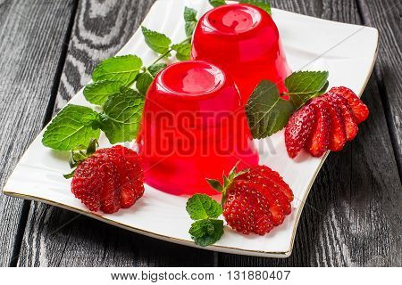 Tasty strawberry jelly and ripe strawberries on plate on a dark wooden table. Selective focus
