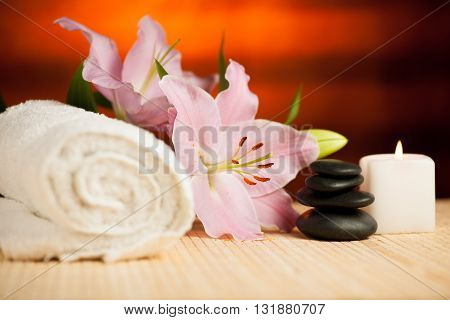 Spa concept of lily flower towels sea salt candle and crystal rock of pink Quartz on warm wooden background.