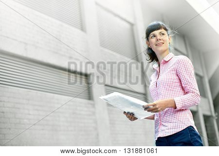 business woman with a folder of papers on a background of gray walls of the building. Business and educational concept
