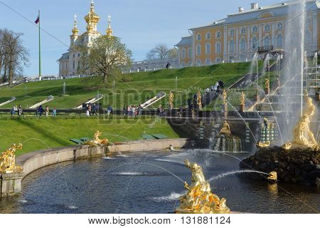PETERHOF, ST. PETERSBURG, RUSSIA - MAY 7, 2016: Tourists walking around the Grand Cascade against Grand Palace. The cascade was built in 1715-1724 and is one of the remarkable fountains in the world