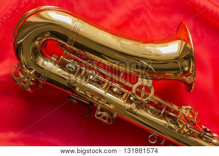 beautiful golden saxophone on delicate red silk background