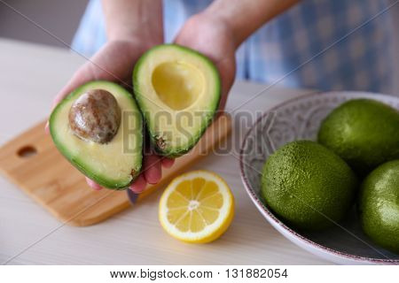 Woman holding fresh avocado in kitchen