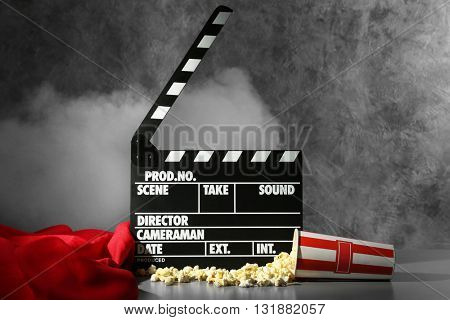 Clapper board and pop corn on wall background
