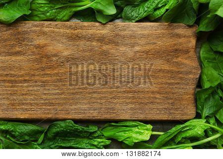Fresh spinach leaves with cutting board