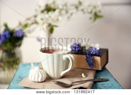 Cup of tea with flowers on wooden stool