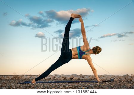 Woman practicing yoga outdoors over sunset sky background