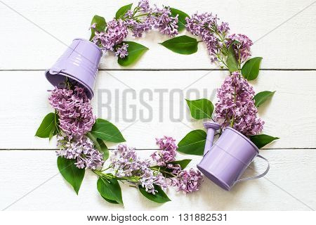 Colorful wreath of lilac with a decorative watering can and a bucket. Use for floral backgrounds holiday greetings and invitations postcard. Top view space for text