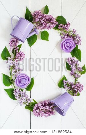 Colorful wreath of lilac with decorative watering can bucket and candles . Use for floral backgrounds holiday greetings and invitations postcard. Top view vertical space for text