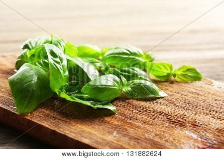 Fresh basil leaves on wooden board