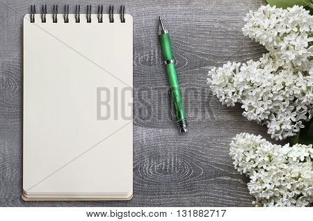 Spiral notebook mockup. Blank notebook with a pen and white lilac on a grey wooden desk