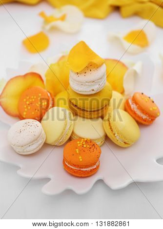 Plate with fresh macaroons and rose petals on light background