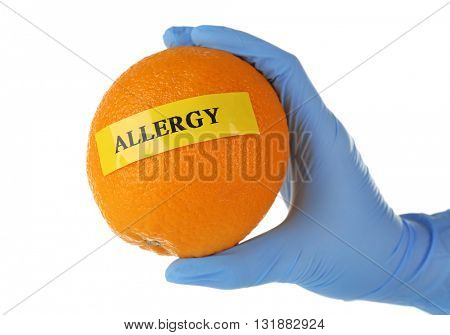 Allergic food concept. Hand in glove holding orange isolated on white