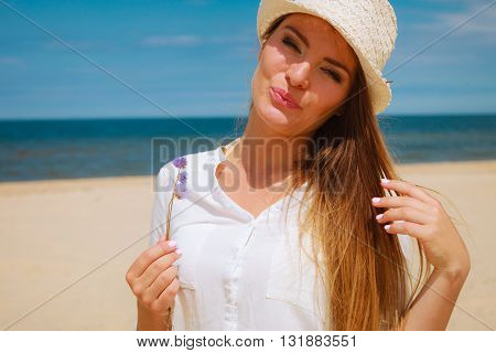 Holidays and vacation. Lovely cute woman tourist holding little flower on sunny beach. Young girl enjoy her free time on seaside.