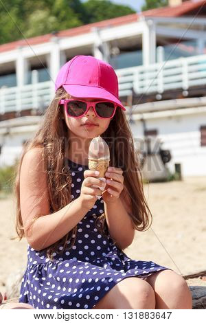 Kid eating gelato soft serve ice cream on beach. Little girl in sunglasses enjoying summer holidays vacation outdoor.