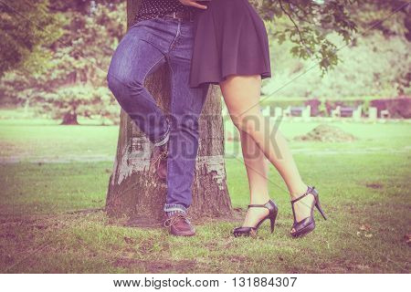 Love and date. Part body of couple lovers dating in summer park outdoor. Filtered photo.