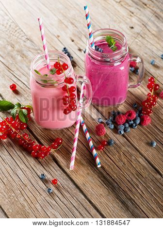 Smoothie of various fresh summer berries (red currant blueberry raspberry) in a mason jar on a rustic wooden background.