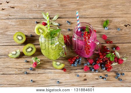 Smoothie and milkshake with variety fresh fruits and berries (kiwi red currant blueberry raspberry) in a mason jar on a old wooden background.