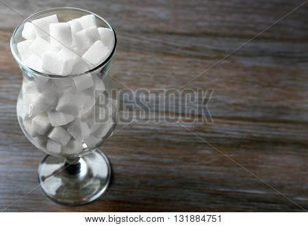 Hurricane glass with lump sugar on wooden table