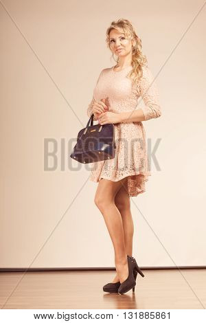Fashion people concept. Coquette woman with beige dress. Lady is holding black handbag and wearing high heels.