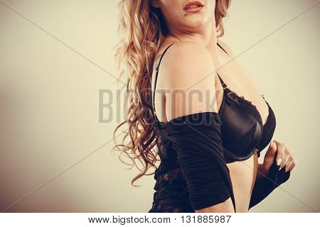 Beauty of female body. Portrait of sexy young blonde woman in black. Long haired seductive girl wearing lingerie.