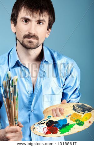 Portrait of an artist holding his brushes and paints. Shot in a studio.